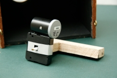 Image shows wooden arm supporting the film canister pinhole camera (no 37) attached to the side of 24hr clock. (nestbox in the background) Copyright Anthony Carr