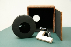 Image shows all parts to Mark III mechanism. The nestbox, the card shutter wheel and the wooden arm supporting both the film canister pinhole camera and 24hr clock. Copyright Anthony Carr