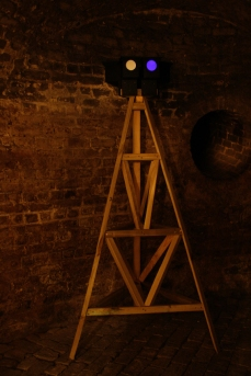 Moonlight Tower (Triangle) in Lumen exhibition, at the Crypt Gallery, London, Dec 2014. Image shows a wooden tower with six low lux moonlight light-boxes at the top. Copyright Anthony Carr